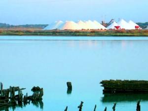 Montes de sal con restos de embarcaciones en primer plano.